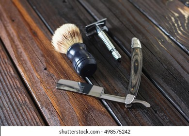 Male Grooming On A Luxury Wooden Background. Mens Safety Razor And Straight Razor With Brush For Shaving.