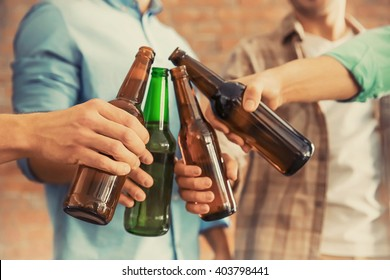 Male group clinking glass bottles of beer on brick wall background