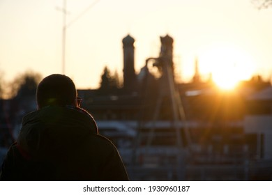 Male Guy walks down a path in the sunset with two Buildings in the back wound matching with the sunset sun. Sunglasses and jacket summer and spring feelings. Sonnenuntergang mann läuft Zwiebelturm