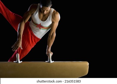 Male gymnast performing on pommel horse