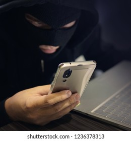 Male hacker in a black mask uses smartphone and laptop. A fraudster commits cyber crime. Fraudulent scheme with personal data and banking. Attempt to make fraud transaction. Cell-phone account fraud.