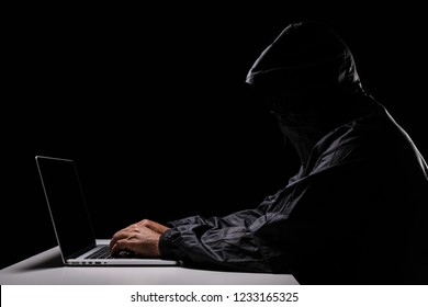 A male hacker cover his head with the hood trying to steal the data from a laptop computer, dark screen version
