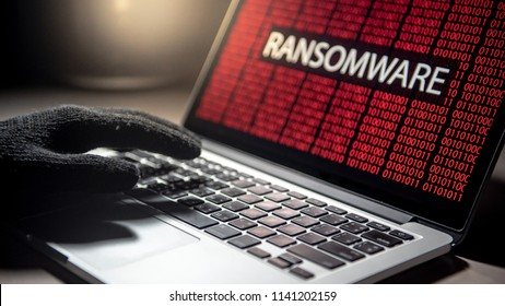 Male hacker hand on laptop computer keyboard with red binary screen of ransomware attacking. Cyber attack and Internet data security concept