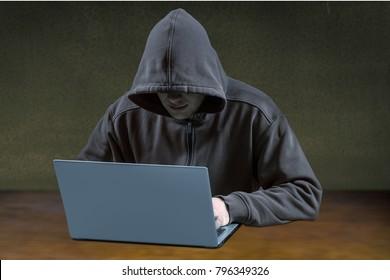 Male hacker working on laptop