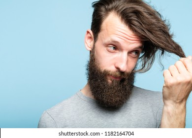 male hair styling problems because of modern hipster and lambersexual fashion. barbershop and hairdressing saloons concept. bearded man portrait on blue background looking at his locks.