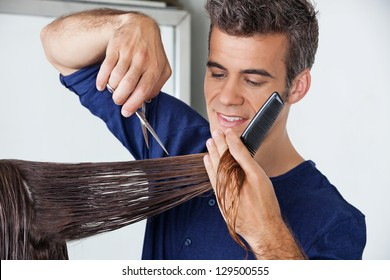 Male hairdresser cutting client's wet hair in salon