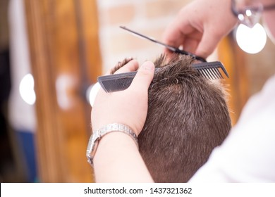 Male hairdresser, grooming men. Haircut styler and trimmer. The master cuts a man, shaves his temples and neck. The client at the hairdresser looks in the mirror. barbershop
