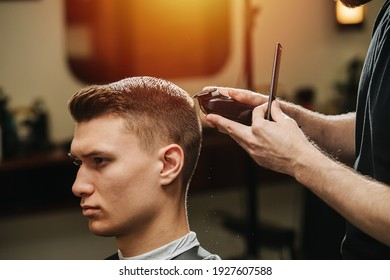 Male hairdresser making a haircut for a young man in a barber shop. He's standing behind client, finishing work with hair clipper. Close up, cropped.