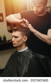 Male hairdresser making a haircut for a young man in a barber shop. He's standing behind client sitting in a chair, combing hair.