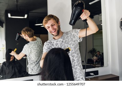 Male hairdresser smiling and talking with a customer while making a new haircut to beutiful young brunette woman