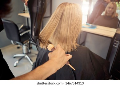male hairdresser styling a beautiful blonde in a salon