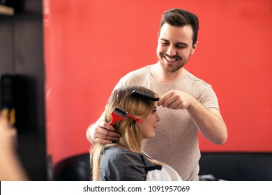 Male hairdresser styling clients hair at beauty salon