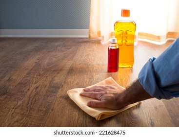 Male hand applying wood care products on hardwood floor surface with a microfiber cloth.