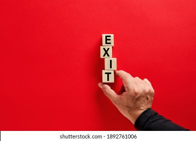 Male hand arranging the wooden blocks with the word exit on red background with copy space. Decision to quit or exit strategy in business concept.