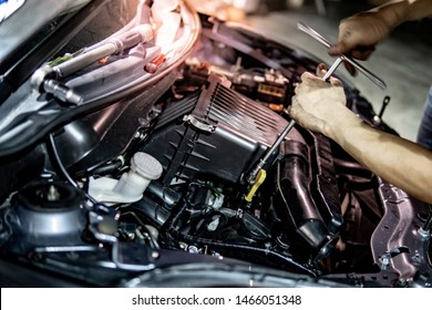 Male hand of auto mechanic fixing car engine in the garage. Automobile industry concept