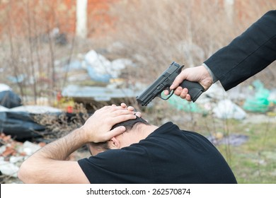 Male hand with black sleeve pointing gun on male head