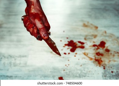 Male hand with bloody knife against the white floor with puddles of blood. Stabbing. Kill with a knife.