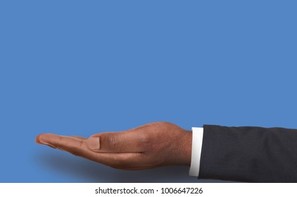 Male hand at blue background with copy space. Empty palm of black businessman holding virtual object, asking or offering something. Conceptual mockup for advertisement, placard or motivation poster