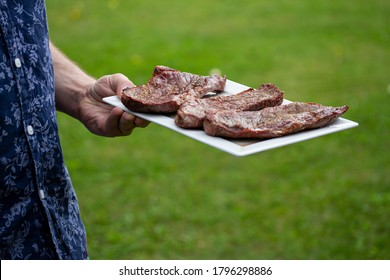 Male hand in blue shirt holding white plate with grilled beef steaks. Green grass background.