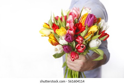 Male hand with bouquet of tulips, isolated on white background