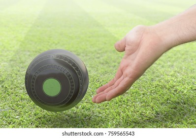 A male hand bowling and releasing a wooden lawn bowling ball on a green lawn grass surface -3D render