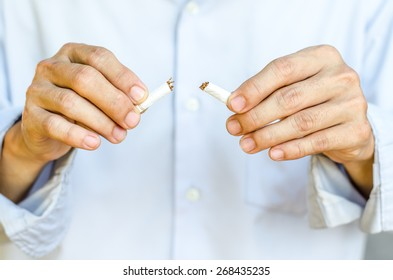 Male hand breaking the last cigarette to stop smoking