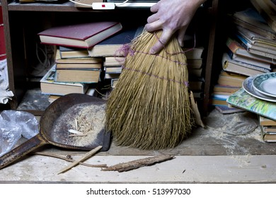 Male hand with broom removing dust and garbage after renovation, closeup indoor shot