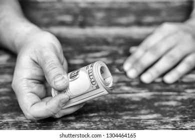 Male hand with a bundle of money.