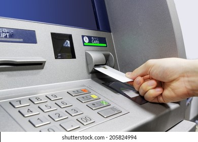 male hand businessman inserts credit card into the ATM and withdraws money