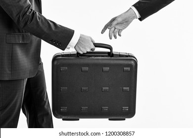 Male hand carry briefcase for exchange or offering bribe. Handover of case in hands of business partners, isolated on white background. Business transfer concept. Male hand in suits hold briefcase.