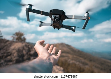 male hand catching drone. Safe quad copter landing on the pilot's palm