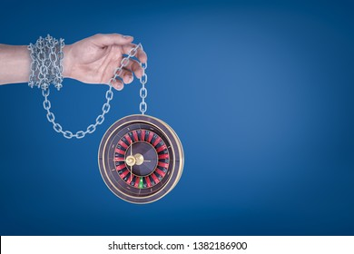 Male hand chained to a roulette on blue background. Gambling and betting. Risk and reward. Bad habits.