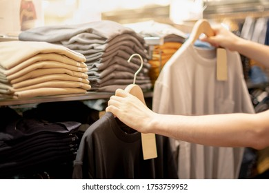 Male hand choosing clothes for checked pattern cotton color of the T-shirt and compare quality on the rack in cloth shop at department store. Check price, discount and promotion of clothing product.