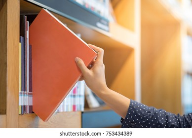 male hand choosing and picking orange book in public library, education research and self learning in university life concepts