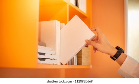 male hand choosing and picking white book on orange bookshelf in public library, education research and self learning in university life concepts