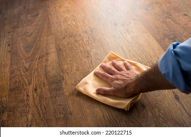 Male hand cleaning and rubbing an hardwood floor with a microfiber cloth.