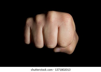Male hand clenched into a fist on a black background