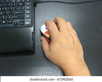 Male hand click Computer mouse with wire network plugged to Laptop