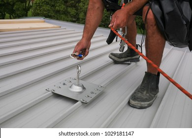 Male hand clipping stainless industrial locking karabiner into the fall arrest roof fixed anchor point systems on construction building site working at height, Sydney city downtown, Australia