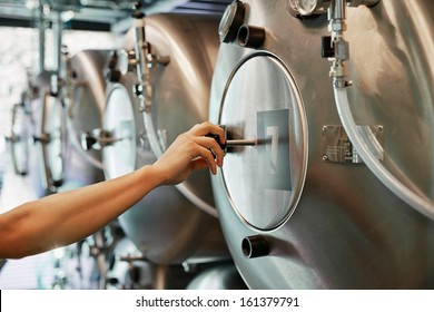 Male hand closes hatch of brewery tank