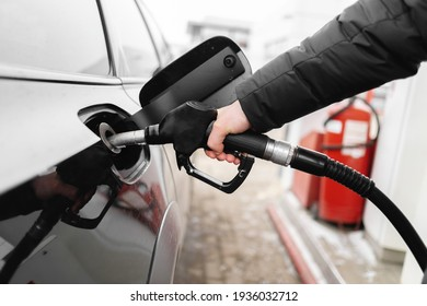 Male hand close-up refueling a black car. higher oil prices