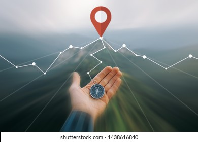 Male hand with compass and connected location GPS pin in summer mountains outdoor, point of view. Navigation concept. Image with moving fast and motion blur effect.