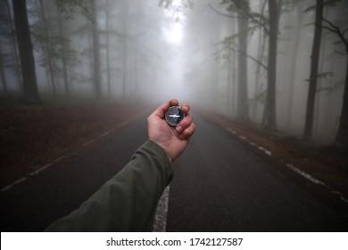 Mano masculina con brújula sobre el fondo del bosque en niebla, punto de vista.