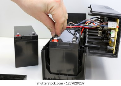 Male hand connects 12 volt battery in uninterruptible power supply. Repair and maintenance of UPS. Replacing battery.
