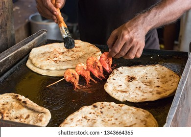 Male hand of a cook, cooking prawns with pol roti flat bread tn the food street market of Galle Face Dr st in Colombo, Sri Lanka.