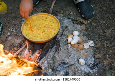 Male hand cooking Menemen in pan on camping fire. Cook chep preparing traditional Turkish food as known Menemen.