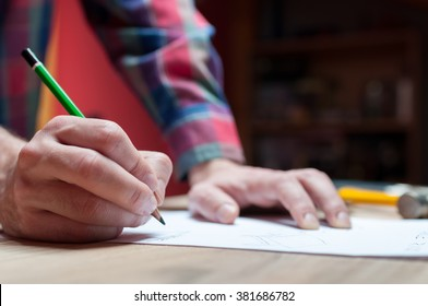 Male hand of a designer with a pen and piece of paper working on a project