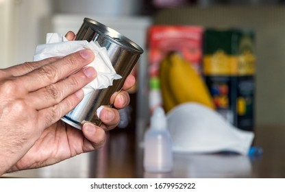 Male hand desinfecting a canned food at home, after greocery shopping.