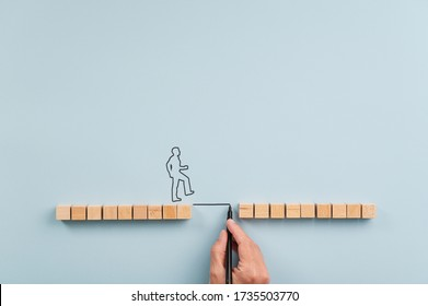 Male hand drawing a bridge between two rows of wooden blocks for a silhouetted man to walk across. Over blue background with plenty of copy space.