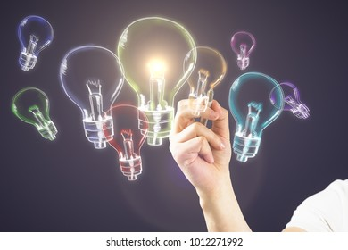 Male hand drawing glowing lamps on dark bakcground. Idea, innovation and inspiration concept